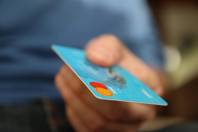 ruka nabízí modrou platební kartu